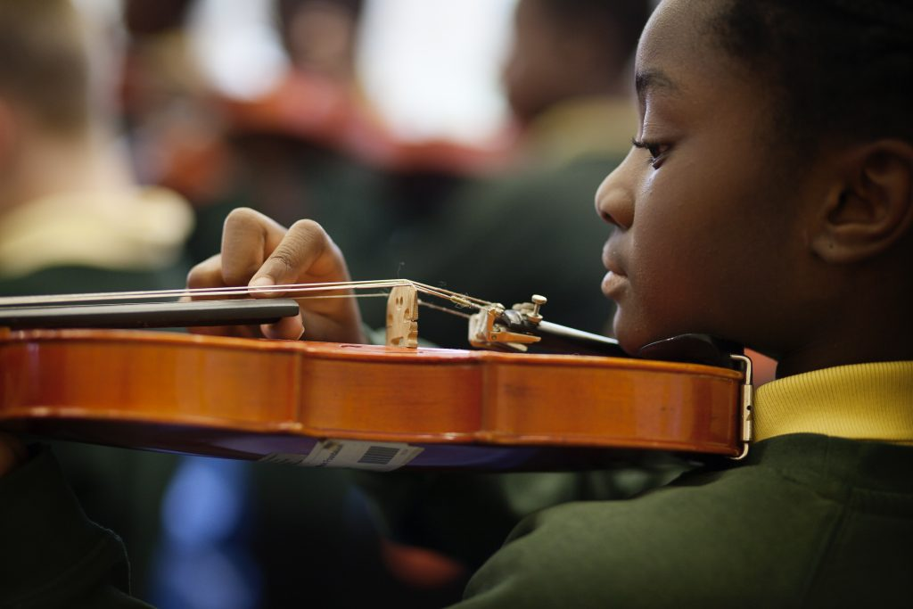 Child having violin lessons with Merton Music Foundation