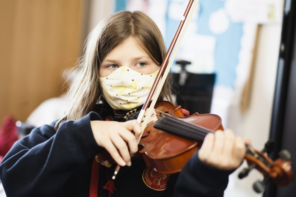 photo of a girl wearing a mask and playing the violin